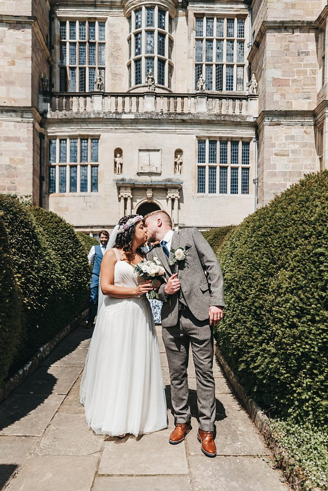 bride and groom pose on steps at Bride and Groom on steps Fountains outside of Hall Fountains Hall Rippon, Fountains Hall Rippon Photos, Fountains Hall Wedding photographer