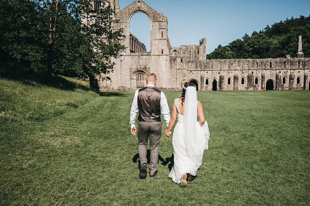 Bride and Groom walk towards Fountains Abbey photograph Fountains Abbey Rippon, Fountains Abbey Rippon Photos, Fountains Abbey Wedding photographer