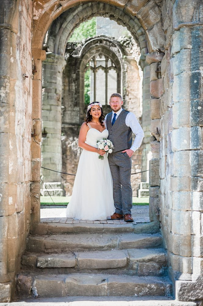 Bride and Groom walk towards Fountains Abbey