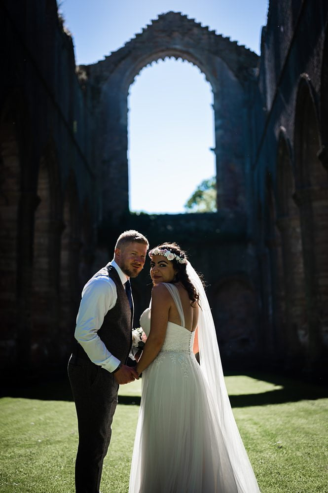 Bride and Groom pose inside Fountains Abbey