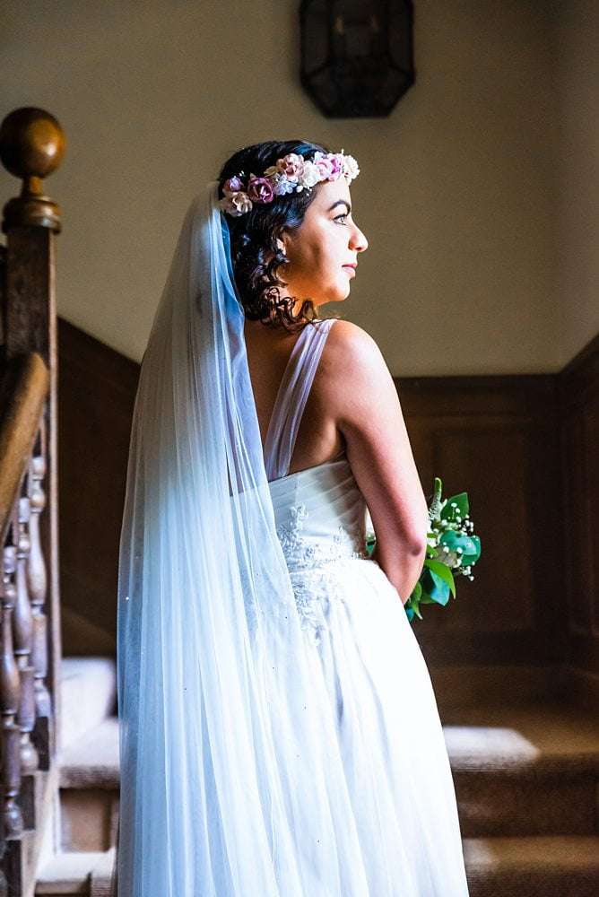 Bride posing halfway up steps looking out of window Fountains Hall Rippon, Fountains Hall Rippon Photos, Fountains Hall Wedding photographer