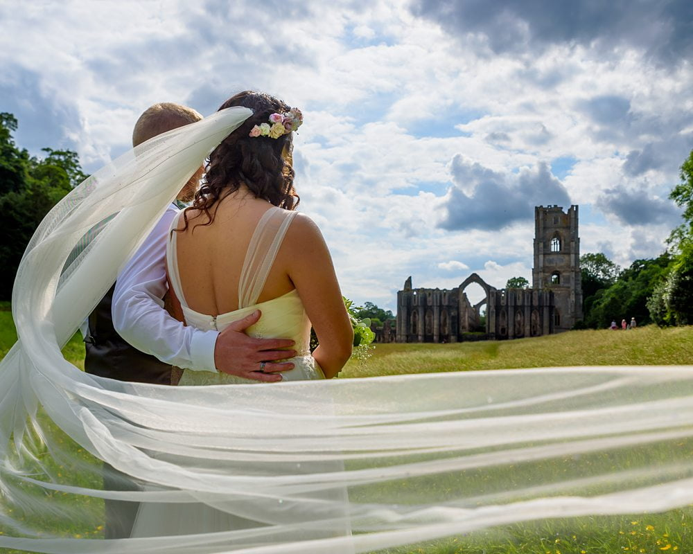Bride and Groom pose with the Abbey in the background Fountains Abbey Rippon, Fountains Abbey Rippon Photos, Fountains Abbey Wedding photographer