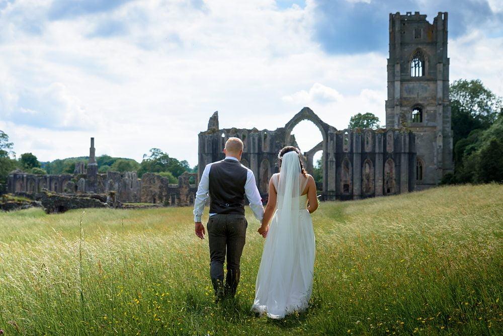 Bride an Groom walk towards Fountains Abbey holding hands Fountains Abbey Rippon, Fountains Abbey Rippon Photos, Fountains Abbey Wedding photographer