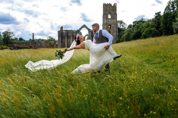 Bride and Groom pose with abbey in background photograph Fountains Abbey Rippon, Fountains Abbey Rippon Photos, Fountains Abbey Wedding photographer