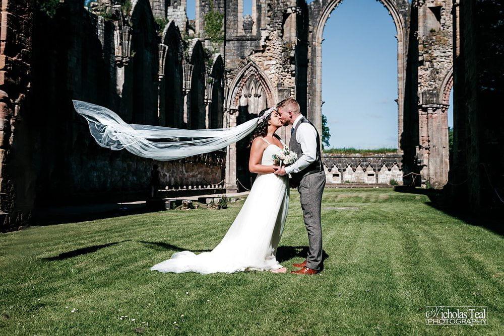 Brides vail blows in win photograph inside Abby walls Fountains Abbey Rippon, Fountains Abbey Rippon Photos, Fountains Abbey Wedding photographer